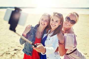 summer vacation, holidays, travel, technology and people concept- group of smiling young women taking picture with smartphone on selfie stick on beach