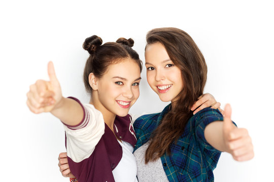 people, gesture and friendship concept - happy smiling pretty teenage girls hugging and showing thumbs up over white background