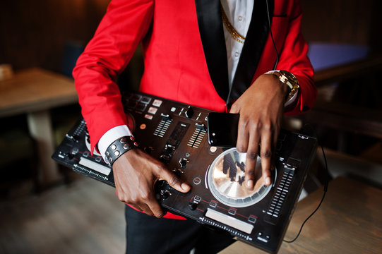 Hands of fashion african american man model DJ at red suit with dj controller.