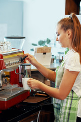 Side view of young woman in apron preparing coffee with brewing machine in modern coffee shop