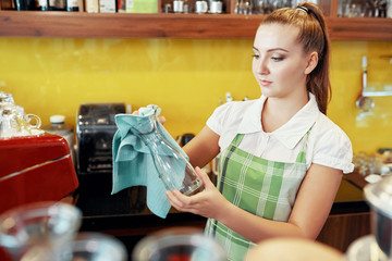 Casual young woman in apron wiping crystal glassware working as barista in modern coffee shop