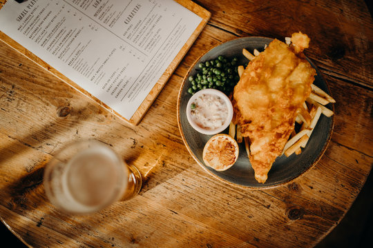 Traditional english fish and chips plate on a wooden table, with a pint and a menu.