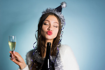 funny drunken young girl celebrates New Year and Christmas, on a hat, holds a glass and a bottle of champagne in her hands, her eyes are closed
