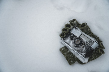 vintage camera on snow and olive-colored gloves, cold winter and snowfall, the end of winter photography