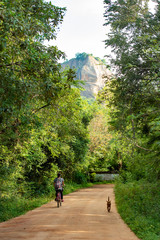 A girl is on her bicycle on the road to the Lion Rock in Sigiriya, Sri Lanka.