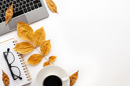 White autumn empty copy space with laptop, coffee, glasses, notebook and yellow leaves. Top view. Concept desk