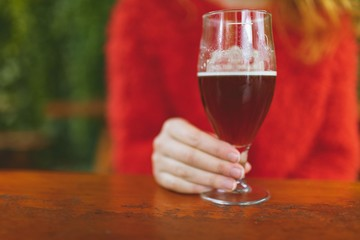 Woman holding a glass of beer in outdoor cafe