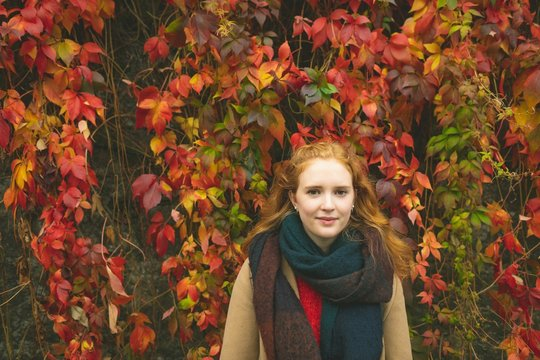 Young woman with blond hair standing against creepers during autumn