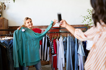 friendship, shopping and technology concept - woman taking picture of happy friend by smartphone at vintage clothing store