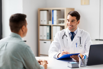 medicine, healthcare and people concept - doctor with clipboard talking to male patient at medical office in hospital