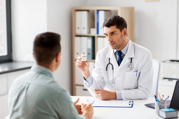 medicine, healthcare and people concept - doctor showing jar with drug to male patient at medical office in hospital