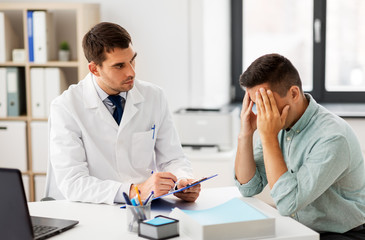 medicine, healthcare and people concept - doctor with clipboard talking to devastated male patient at medical office in hospital