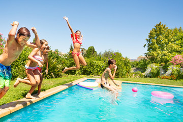 Group of friends jumping in outdoor swimming pool