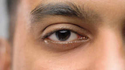 vision and people concept - close up of south asian male eye with brown iris