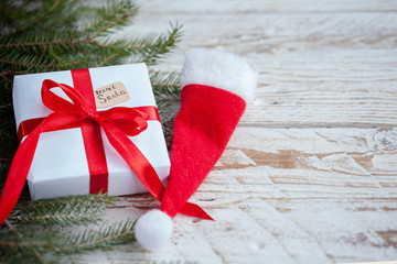 Christmas white box or present with red ribbon for secret santa with santa hat on wooden table.