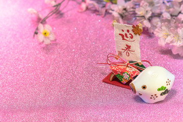 Glitter background for japanese New Year's Cards with cute animal figurine of boar or pig and rice paper with handwriting ideograms Geishun which means Welcome Spring.