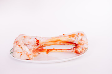 on white plate in a white dish lies bone with meat in blood