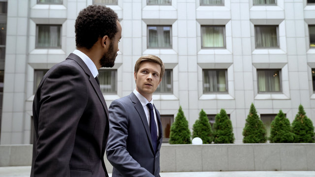 Multiracial coworkers walking near business center, discussing issues at break