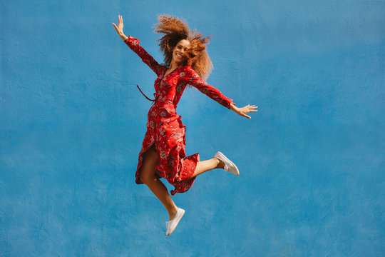 Beautiful woman in sundress jumping with joy