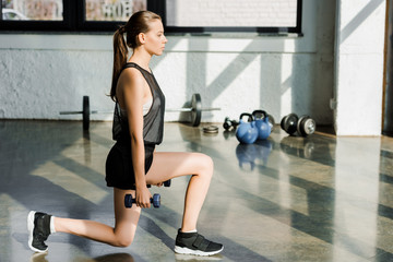 attractive athletic sportswoman doing lunge exercise with dumbbells at fitness center