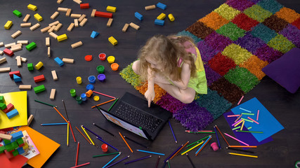Blond curly preschool child watching cartoon on laptop, sitting on floor