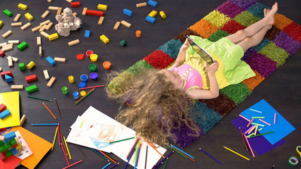 Blond little girl with blond hair lying on colorful carpet and playing on tablet