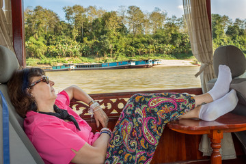 Woman having a nap in a boat while cruising in Nam Kahn River