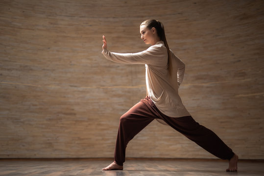 Serious young woman standing alone with her hand in front of her and looking concentrated during chi gong practice