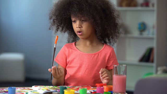 Cute african girl painting at workshop, leisure activity and art, preschool club