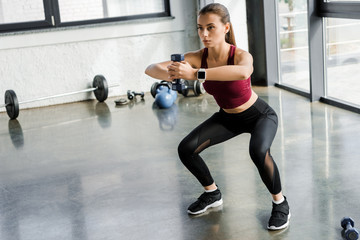 focused sportswoman doing squat exercise with dumbbell at sports center