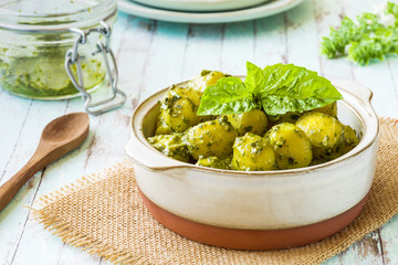 Gnocchi with 'Pesto' sauce, in terracotta bowl, on rustic background..