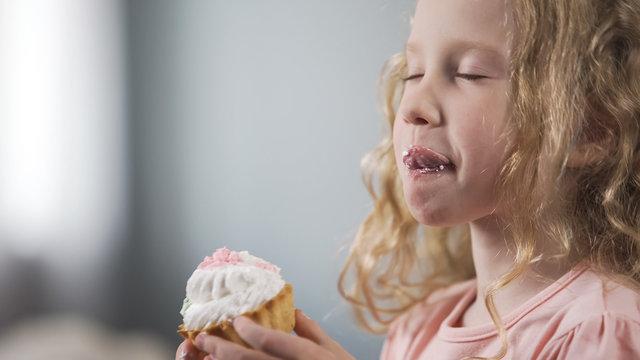Adorable little girl eating cake with appetite enjoying perfect taste of dessert