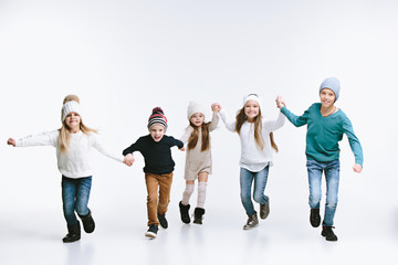Group of kids in bright winter clothes, isolated on white studio. Fashion, childhood, happy emotions concept