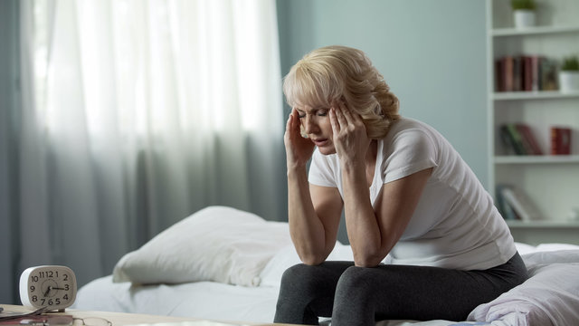 Senior woman sitting on bed and suffering from terrible headache, health problem