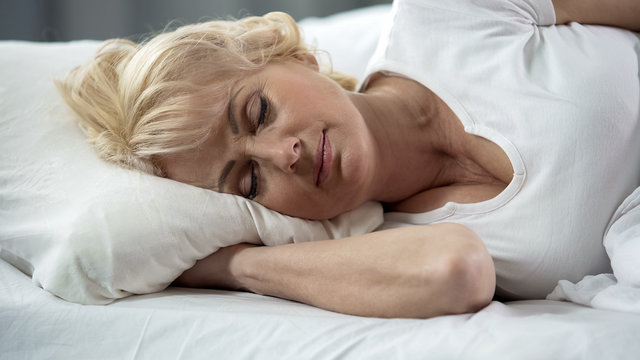 Beautiful blond mature lady lying in bed close-up, healthy sleep, retirement