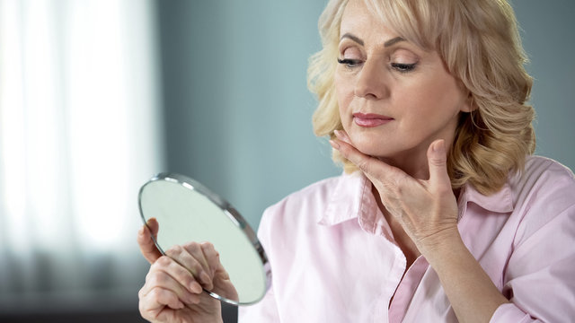 Attractive aged woman looking at her face in mirror, plastic surgery effect
