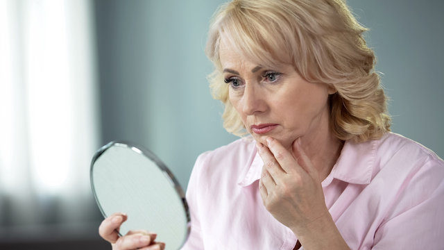 Unhappy senior female looking at sagging skin face in mirror, old age appearance
