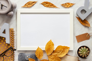 Autumn composition background. Artist home office desk workspace, frame, autumn leaves, cactus, concrete alarm clock, notebook, letters. Flat lay, top view creative minimal mock up template.