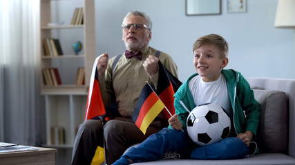 Boy and grandpa holding German flags, watching football, worrying about game