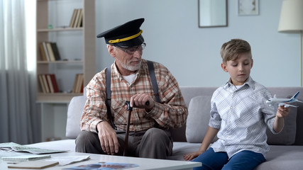 Boy playing with toy airplane, grandpa former pilot proud of grandson, dream job