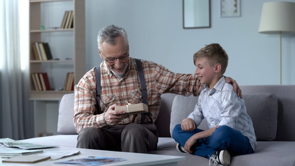 Grandson giving present to grandfather, attention and care for loved ones