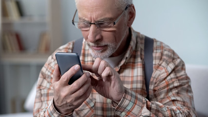 Old man cautiously using smartphone, learning apps and new technologies, closeup