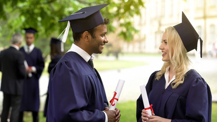Couple of graduate students with diplomas talking and smiling to each other