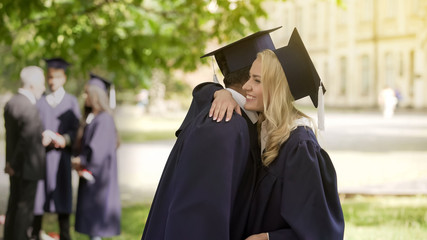 Classmates in graduation outfit talking, hugging and congratulating each other
