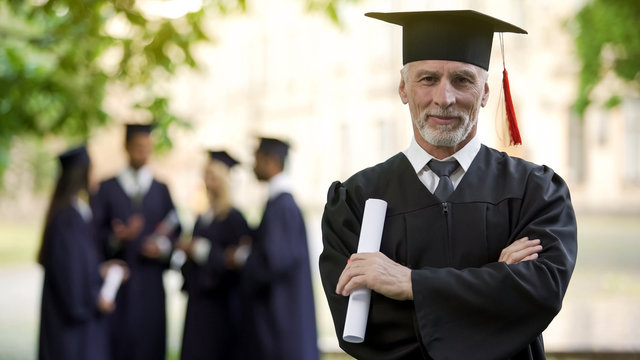 Confident man in graduation outfit, male obtaining degree, academic career
