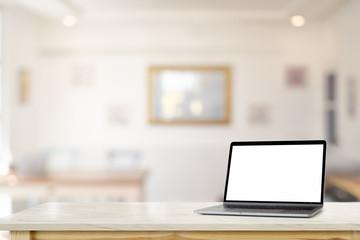 Mockup blank screen laptop on marble desk table over living room.