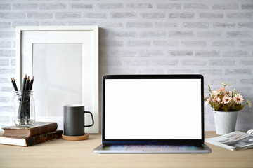 Creative desk workspace with blank picture frame poster, blank screen laptop for graphic display montage