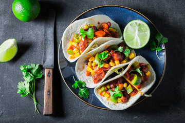 Mexican tacos with meat and lime on concrete table