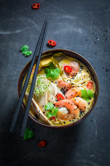 Hot Malaysian Soup with prawn on concrete table