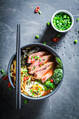 Delicious Ramen soup with beef and eggs on concrete table